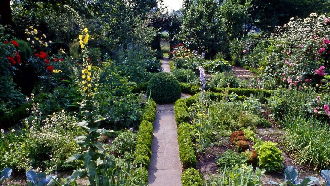 Ein blühender Bauerngarten mit Wegekreuz.