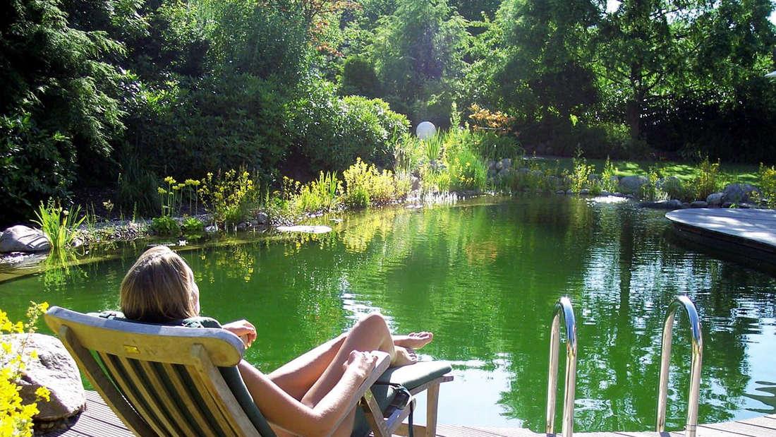Zu sehen ist ein angelegter Schwimmreich, an dessen Rand eine Frau in einem Liegestuhl liegt und auf den Teich blickt (Symbolbild).