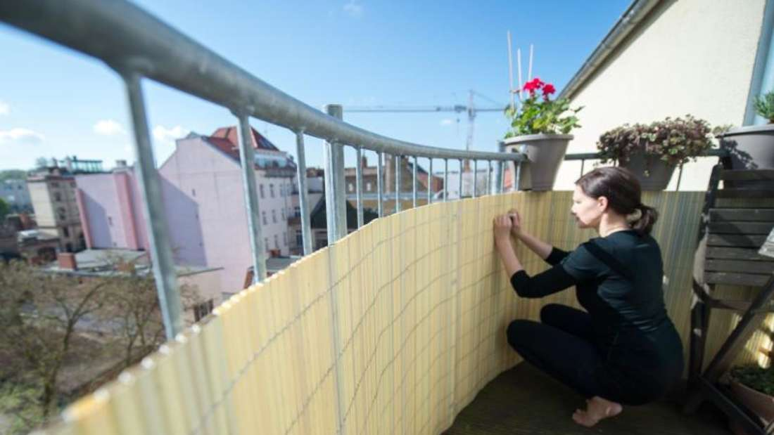 Zu sehen ist eine Frau, die auf ihrem Balkon kniet und am Geländer einen Sichtschutz montiert (Symbolbild).