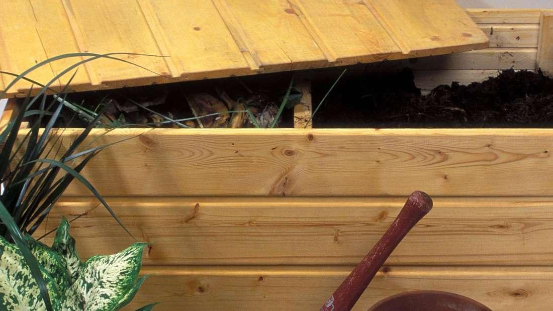 Eine Wurmkiste mit zwei Kammer und offenem Deckel. Davor eine Schaufel, Töpfe mit Erde und eine Pflanze.