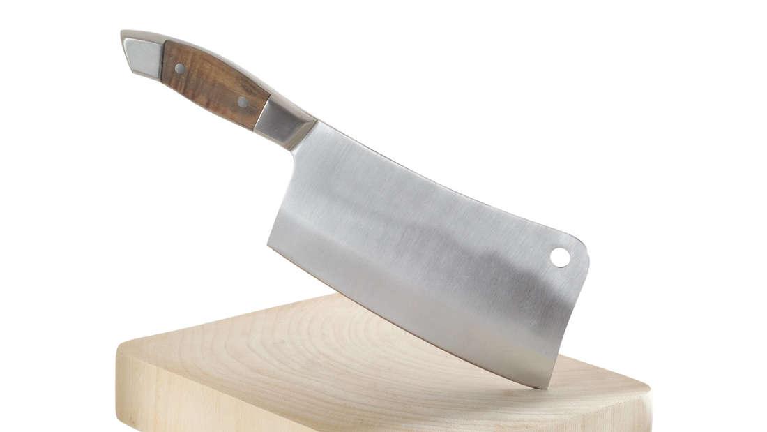 Zu sehen ist ein großes Fleischbeil, das in einem Holzblock steckt.
