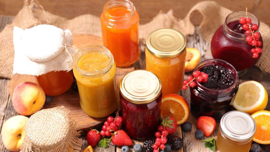 Von oben fotografiert stehen auf einem groben Holztisch verschiedene Gläser mit Marmeladen in verschiedenen Farben gefüllt. Dazwischen verschiedene Früchte.