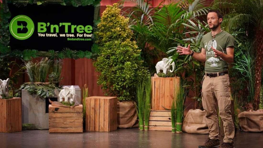 """Chris Kaiser präsentiert sein Unternehmen """"B'n'Tree"""" bei """"Die Höhle der Löwen"""". Im Hintergrund stehen viele Holzkisten, die mit Pflanzen befüllt sind."""
