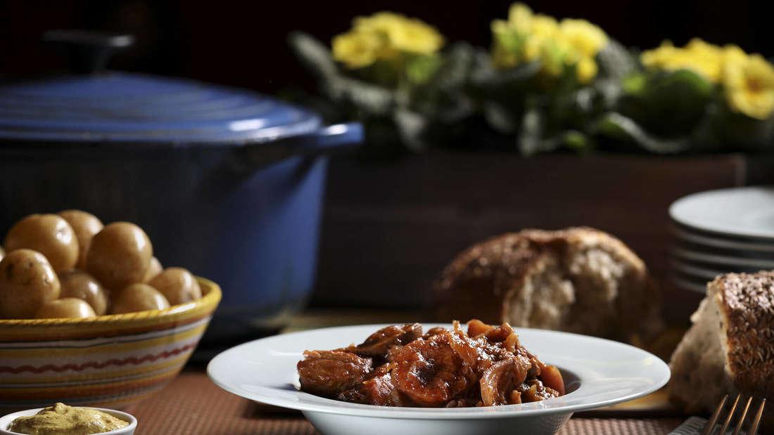 Ein weißer Teller mit Bigos auf einem Tisch. Dahinter steht eine schale mit Kartoffeln, eine schale mit Senf und etwas Brot (Symbolbild).