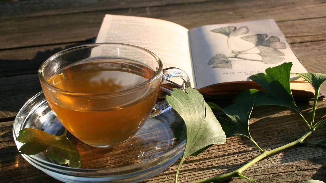 Zu sehen ist eine Glastasse, die mit bräunlichem Tee gefüllt ist. Daneben liegen grüne Ginkgo-Blätter und im Hintergrund ein aufgeschlagenes Buch (Symbolbild).