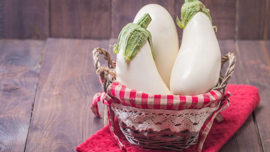 Zu sehen sind drei längliche weiße Auberginen in einem Korb auf rotem Tuch und Holztisch (Symbolbild).