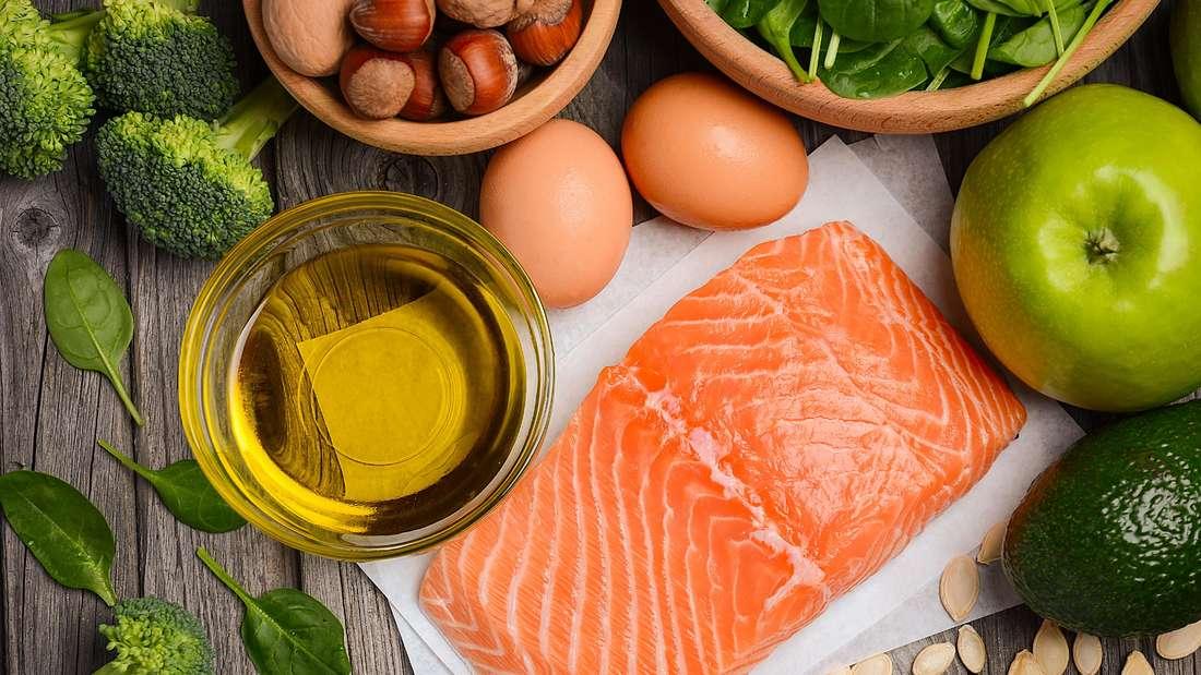 Zu sehen sind Lebensmittel wie Lachs, Öl, Äpfel, Avocado, Eier, Kürbiskerne, Nüsse, Brokkoli und mehr (Symbolbild).