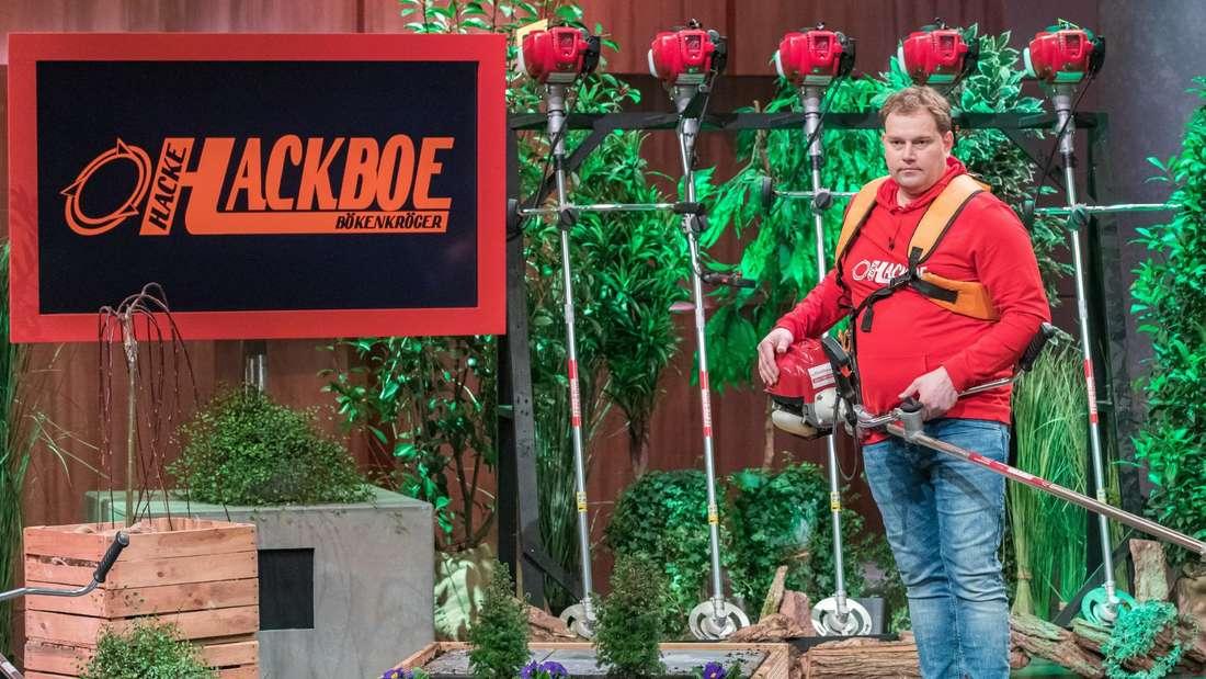 """Zu sehen ist Mike Bökenkröger, der seine Garten-Motorhacke um den Oberkörper geschnallt hat und sie in der TV-Show """"Die Höhle der Löwen"""" präsentiert."""